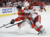 Chicago right wing Michael Frolik (67) is checked by Phoenix defenseman Adrian Aucoin (33) during the NHL game between the Chicago Blackhawks and the Phoenix Coyotes at the United Center in Chicago, IL. The Coyotes defeated the Blackhawks 4-3 in a shootout.