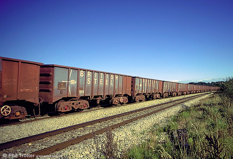 A batch of 114 JUA wagons was built in 1974 for the Port Talbot to Llanwern iron ore trains. This service was also noted for its weight; rakes of 27 wagons needed three class 37s, although pairs of 56s were later able to manage 30 wagons - a 3304 tonne load of iron ore. This rake is seen at St. Georges, west of Cardiff.