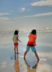 Standing On Clouds -- Roads End Beach, Oregon Girls waiting for the ocean waves as they stand in the reflection of the clouds above...
