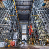 """<h2>The Megahangar at NASA</h2> <br/>Imagine a giant skyscraper, but hollow and filled with people making rockets.  That's what the VAB is.  To really get a sense of the size of this thing, look at the outline of the man standing in the distance, his body backlit by the door. <br/>The VAB, or Vehicle Assembly Building, is the worlds largest single-story building, and it's where NASA assembles many of the rockets, including the mighty Saturn V.  It's also the tallest building in the US that's not in a downtown area.   It's situated at Launch Complex 39 at the Kennedy Space Center, and it's awesome dot com. <br/><br/>The thing is so big that it even has its own weather system.  In fact, <em>on humid days it can even rain inside the building</em>!  In my photo below, you are really only seeing part of it.  Off to the right, they are fueling up the Atlantis for its upcoming mission.  Staring through the girders from another angle, you can easily see the giant orange tank going through its pre-launch ordeal.<br/><br/>Getting into this place was very difficult.  I felt privileged to even get through the various security screenings and get the governmental approval to go inside.  They let in little groups of us from the Tweetup, and I have to thank Stephanie Schierholz for making it all happen.  It's one of the mysterious places on earth I've always wanted to visit, so I was very excited to be inside.  My next goal is to get back inside and get up higher... perhaps even get in while they are prepping the next rocket.<br/><br/>I have many more shots of this building that I'll be sharing in coming weeks and months... you guys know how I like to keep these threads and stories open for a long time!<br/><br/>- Trey Ratcliff<br/><br/><a href=""""http://www.stuckincustoms.com/2011/05/08/webinar-grand-prize-destination-austin-with-trey/"""" rel=""""nofollow"""">Click here to read the rest of this post at the Stuck in Customs blog.</a>"""