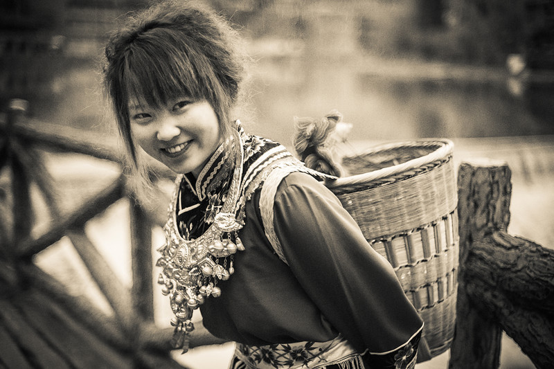 "<h2>Girl Carrying Basket in China</h2> <br/>These out-of-the-way places are some of the best for photography because the locals actually like photographers from the west. About 98% of the time they find us interesting and worthy of a smile. They seem to like the attention we give them with our cameras and there are many smiles to be had.<br/><br/>I don't take a lot of photos of people smiling, because I like to take photos before people notice or right as soon as they notice. Usually though, everyone smiles after I take a few… I do a few facial maneuvers so that they feel more comfy.<br/><br/>- Trey Ratcliff<br/><br/><a href=""http://www.stuckincustoms.com/2012/09/04/girl-carrying-basket-in-china/"" rel=""nofollow"">Click here to read the rest of this post at the Stuck in Customs blog.</a>"