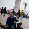 """<h2>Boy and Grandfather at Tiananmen Square</h2> I was walking through Tiananmen on a white-out cloud day taking photos of people. I had on my earphones and was kind of drifting in and among the crowd. It's a bit like being in a movie when you do this... anyway, I'm sure you've heard me mention it before, so I won't go into details.  It's often a very nice way to make things timeless... to separate people and objects from their place and time.  These two were on the ground wrestling and having fun.  I squatted about 15 feet away to take a photo, and they were most delighted!  - Trey Ratcliff  From the <a href=""""http://www.stuckincustoms.com/2011/09/12/boy-and-grandfather-at-tiananmen-square/"""">blog post</a> at www.stuckincustoms.com."""