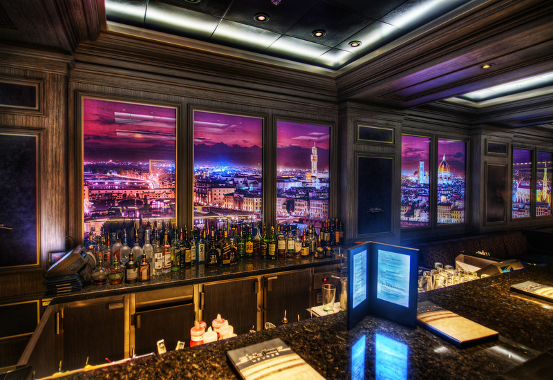 """<h2>Disney Fantasy Cruise - The Skyline Bar</h2> Which city do you think this is??<br/><br/>This is the coolest bar on the ship.  I was in here this night with John Lasseter (I think!) - but he was sitting with a group of people and I didn't want to interrupt him to say hello.  Anyway, these walls are filled with images of different cities that change out every 12-14 minutes or so.  And, if you get up close to these hi-def walls, you can see movement!  People walk around the streets, cars move, lights flicker, people go about their days inside their homes, etc.  It's endlessly fascinating.  I also have some video of this too -- I'll release that as soon as I have more bandwidth at dock!<br/><br/>- Trey Ratcliff<br/><br/><a href=""""http://www.stuckincustoms.com/2012/04/06/disney-fantasy-cruise-the-skyline-bar/"""" rel=""""nofollow"""">Read the rest of this post at the Stuck in Customs blog.</a>"""