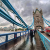 """<h2>Crossing Tower Bridge in the Rain</h2> <br/>My bulbous 14-24 lens is a problem in the rain!  If you haven't seen the Nikon 14-24 (see my <a href=""""http://www.stuckincustoms.com/nikon-14-24-review/"""">Nikon 14-24 Review</a>) before, then most people think it is a fish-eye lens, but it isn't.  The apex of the glass juts out almost just beyond the tiny bayonet, and it seems to suck rain drops into it!  I'm always wiping down that dang thing.<br/><br/>But... here's another little hint.  That lens can shoot at F/2.8.  That means you can focus on infinity for most of your landscape shots, and you'll only see a few, if any, raindrops that form on the lens.  It's a very nifty trick!  And, with a wide-angle lens, infinity ain't that far away.<br/><br/>- Trey Ratcliff<br/><br/><a href=""""http://www.stuckincustoms.com/2011/03/06/crossing-tower-bridge-in-the-rain/"""" rel=""""nofollow"""">Click here to read the rest of this post at the Stuck in Customs blog.</a>"""