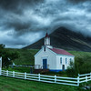 "<h2>The Boiling Heavens</h2> <br/>The weather was wet and heavy.  It had that feeling that it will rain any minute, and every minute it did not rain felt like a lucky break. <br/><br/>This church sat up high on a hill in NW Iceland and could not be seen from the street.  I happened to turn up a little driveway and found it at the top.  You can't see it from this angle (it was impossible to compose), but those homes on the left have grass roofs. <br/><br/> - Trey Ratcliff <br/><br/>Read the rest of this at the <a href=""http://www.stuckincustoms.com/2010/07/02/the-boiling-heavens/"">Stuck in Customs blog.</a>"