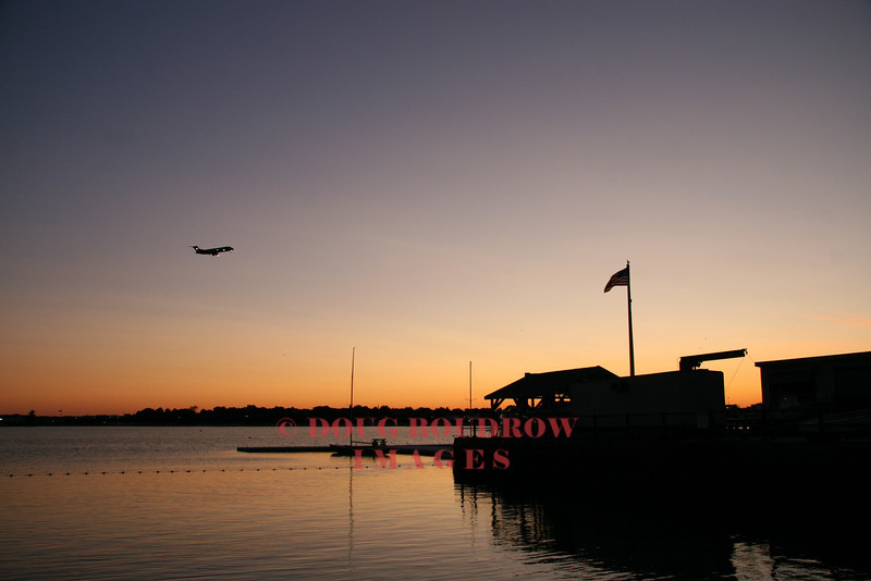 Boston, MA - An airliner on final approach to Logan International passes Castle Island at dusk, 9-1-08.