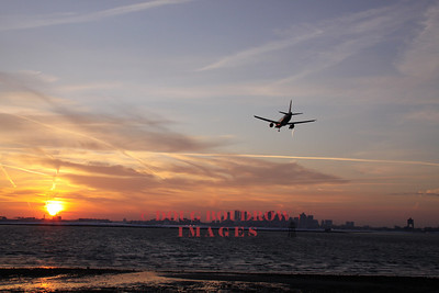 Winthrop, MA - A 737 lands at Boston Logan Airport as the sun goes down over South Boston, 1-22-09.