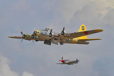 A B-17 Flying Fortress with a P-51 escort