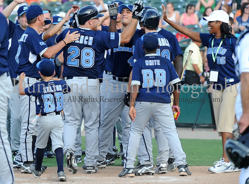 Former Texas Ranger Kevin Mench is congratulated by teammates after hitting a home run in the Reebok 2011 Heroes Celebrity Baseball Event