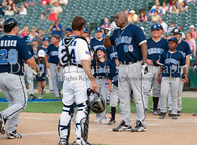 Former Texas Ranger Kevin Mench is congratulated by Actor Michael Clarke Duncan and other teammates after hitting a home run in the Reebok 2011 Heroes Celebrity Baseball Event