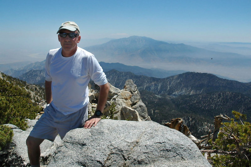 Me on top of Bighorn Mountain at 10,997 feet with San Jacinto Peak in the background. That small black dot on the right side of the photo is one of the hundreds of ravens that were flying over the peak.
