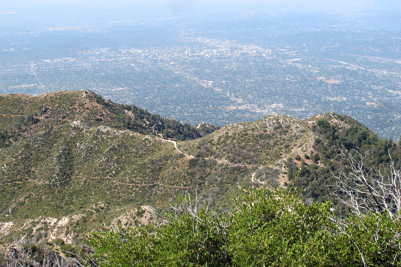 To the south on the saddle is Inspiration Point 1,100 feet below. The peak to the right is Muir Peak 4,714'. The area with the large buildings is downtown Pasadena.