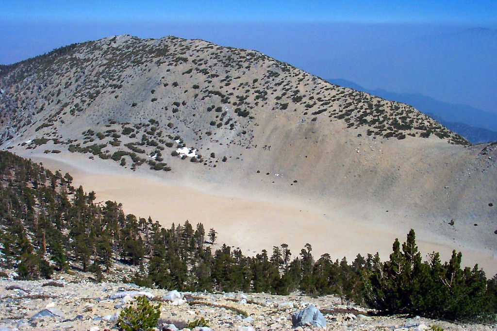 """Looking down on """"The Tarn"""" from the trail. Located at 10,560 feet just southeast of the summit. When melting snow fills it each spring, it becomes the highest lake in southern California. The peak behind it is Bighorn Mountain."""