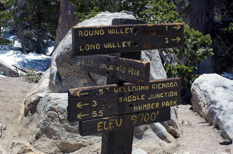 The sign shows 2.3 miles to the peak.