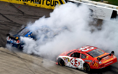 Martin Truex Jr spins after exiting turn one at Martinsville Raceway.  Reed Sorensen drops low to avoid him.