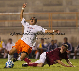 Mario Alvarez (14) is tackled hard by Jack Henderson (23).  Cal State Fullerton beat Denver University 4-2 at Titan Stadium, Fullerton.