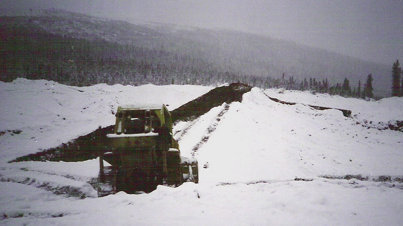 Bleak? You bet. Here, we've scraped off the overburden, pushed it up the hill to the left, and the Terex is ready to scrape a load of supposed paydirt up to the sluice. The box is on the left, connected by several hundred feet of hydraulic pipe to a pump in an ice-free eddy in the creek. The sluice itself runs down to the impoundment in Butte Creek on the right.  And if it <I>looks</I> bleak, it's hard to describe how far things deteriorate when you add another sense. Placer mines stink. There are a lot of places where you can be overwhelmed by Diesel, but placer mines add a pervasive stench of thawed Pleistocene organic material that's been munched on for centuries by anaerobic bacteria. It's a memory that never leaves. Well, maybe never. It's one of the things I look forward to with Alzheimer's.
