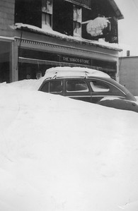 2009.033.1.14--print 3x4.5--C&NW--car buried in snow in front of Kellner Hardware store--Cuba City WI--1953 0100