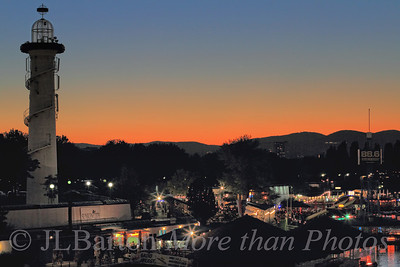 """Vienna by Night 2011-09-07  A sunset shot of the outdoor eating/drinking/dancing area on the """"Danube Island"""", with the hills of the Vienna Woods in the background.  The 'lighthouse' was a prop as part of the """"Flying Dutchman"""" production at the Bregenz opera years ago, and now serves just as a landmark.  And thanks for the comments and the perseverance yesterday."""