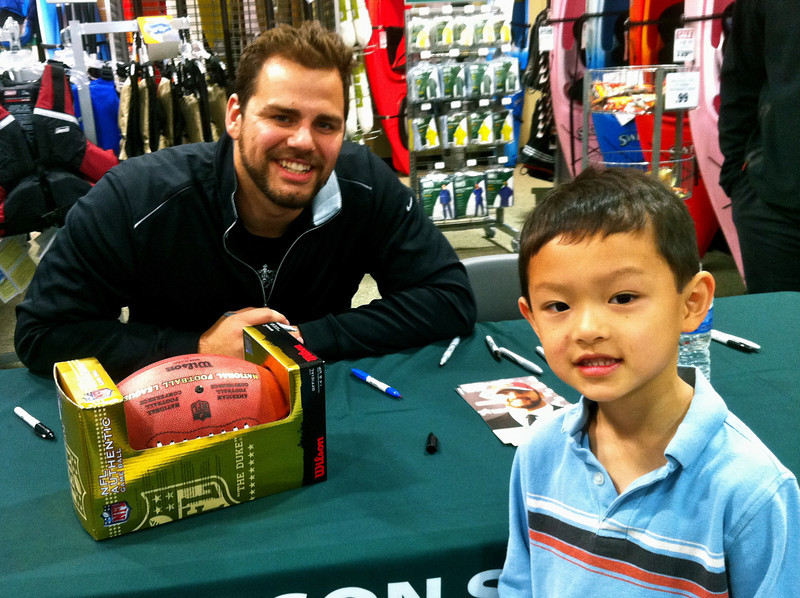 """Gabe Carimi, 23, signs autographs October 31, 2011 at the grand opening of Dick's Sporting Goods in Naperville, Illinois. Carimi, who stands at 6'7"""" and weighs 316 lbs, plays tackle (#72) for the Chicago Bears. Ethan, 7, who stands at 3'9"""" and weighs 40 lbs, plays defender and midfielder for a Naperville Park District soccer team."""