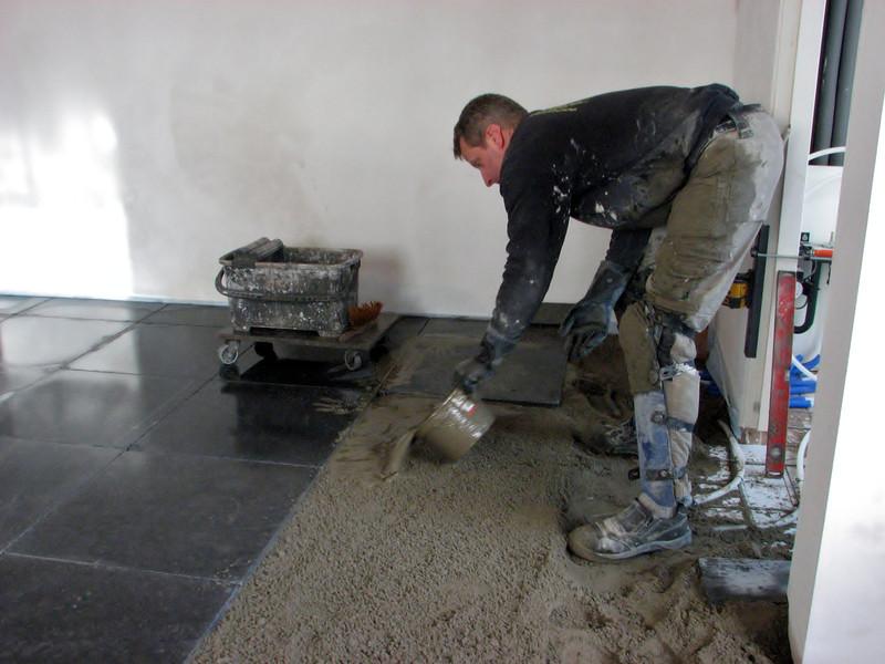 Toine Adriaans tiling the kitchen floor with bluestone (Avedo tegelwerken)