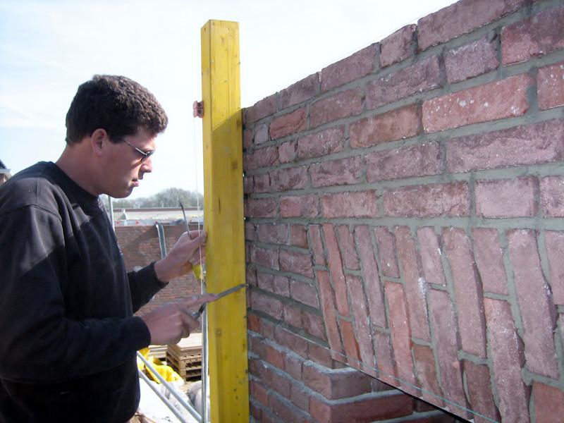Twan bricklaying the bricksupright course of the garage door (width 2,5 m. R 3,75m.) (NL: strekse boog voor de garage deur)