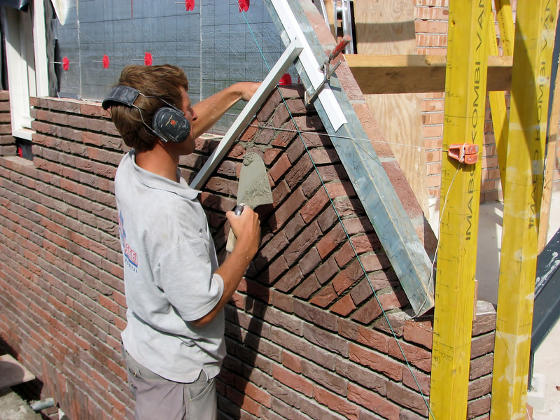 "Paul and Twan bricklaying the upright course (NL: ""boerenvlecht"") of the gable"