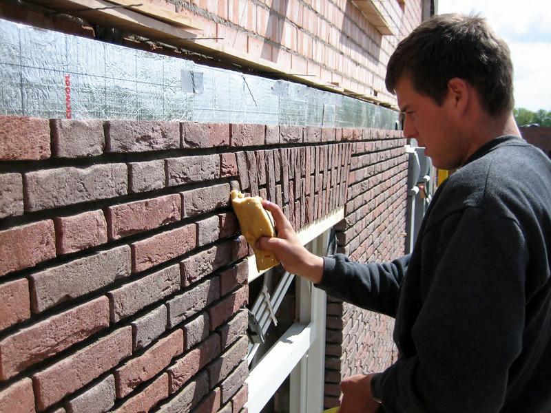 Erik van Gastel (NL: van Erik van Gastel metsel- en timmerwerken) cleaning the right side wall of the house