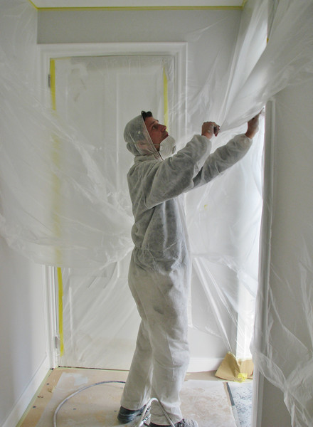 Taping up before spraying the walls and ceiling (firm: Robert v.d. Wetering schilderwerken)