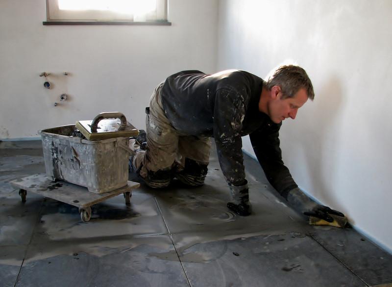 Toine Adriaans is washing in the kitchen floor (Avedo tegelwerken)