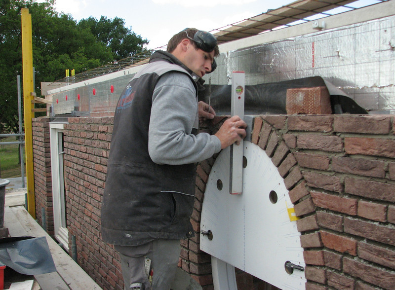 Bricklaying and measuring the top stone