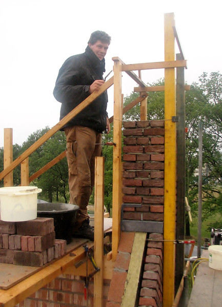 Paul  and Twan bricklaying the chimney on the gable top (in bad weather)
