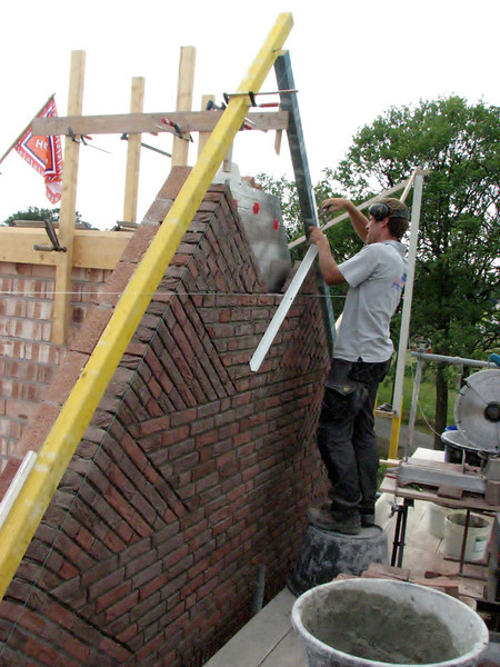 "Paul bricklaying the upright course (NL: ""boerenvlecht"") of the gable end"