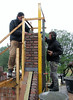 Paul  and Twan bricklaying the chimney on the gable top