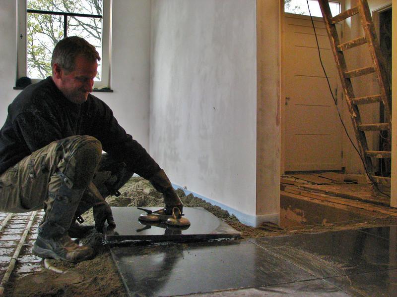 Twan tiling the kitchen floor with bluestone (Avedo tegelwerken)