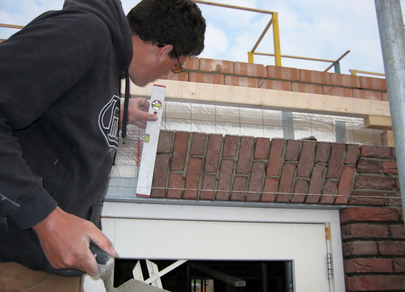 Twan bricklaying the upright course on the rear side of the house