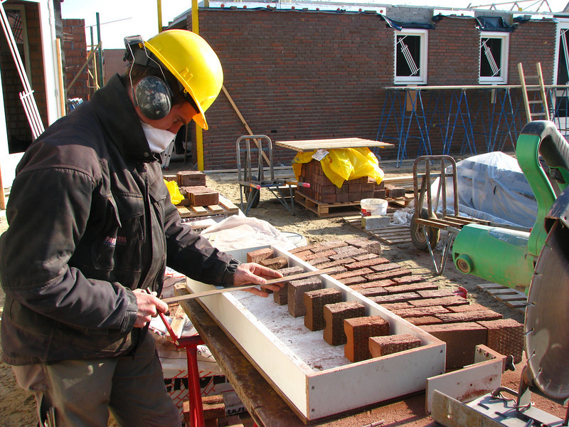 Paul grinding the stones of the bricksupright course of Frans garage windows