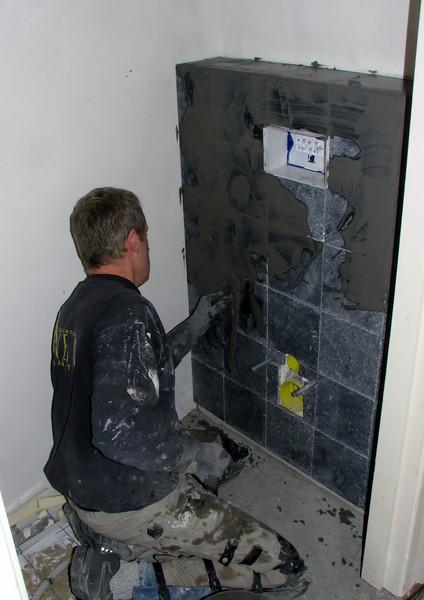 Toine Adriaans is washing in the toilet wall (Avedo tegelwerken)
