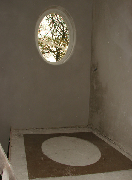 Plastered oval window frame with the used template on the floor