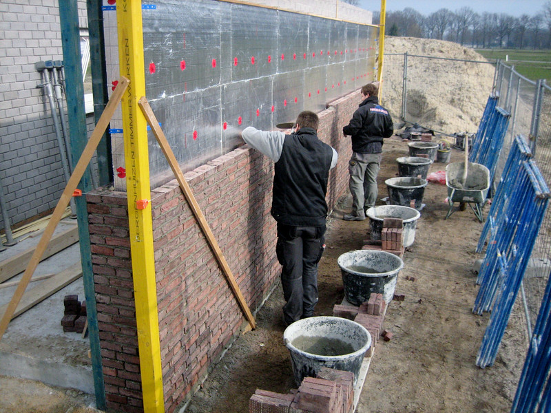 The Van Gastel brothers bricklaying the outside walls of the garage