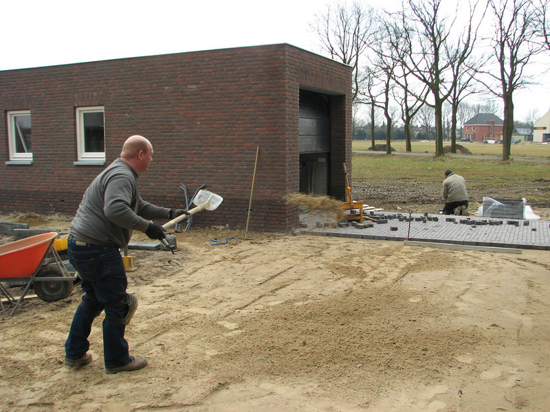 Henk Driessen paving the surface around the house