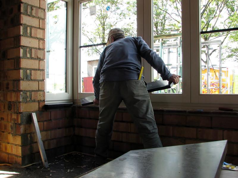 Marijn mounting the inside windowsills of the bay. Belgian bluestone.