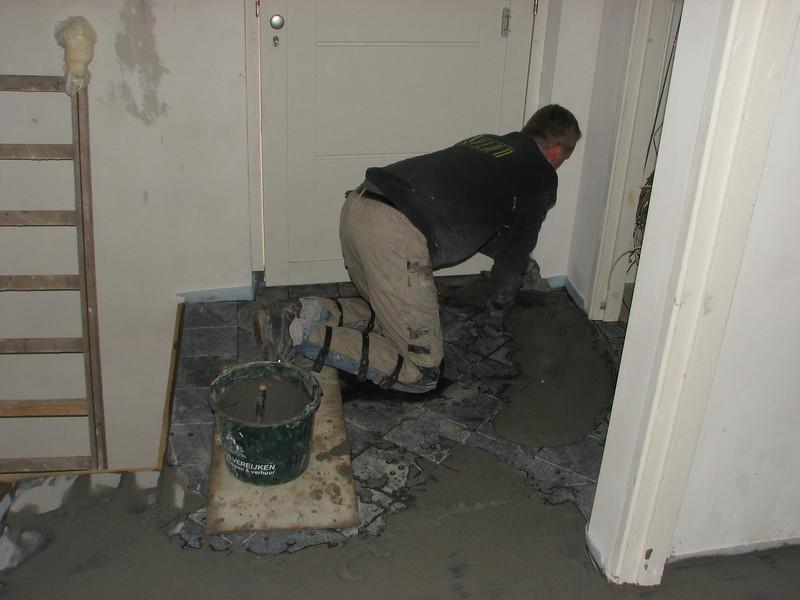 Toine Adriaans is washing in the hall floor (bluestone) (Avedo tegelwerken)