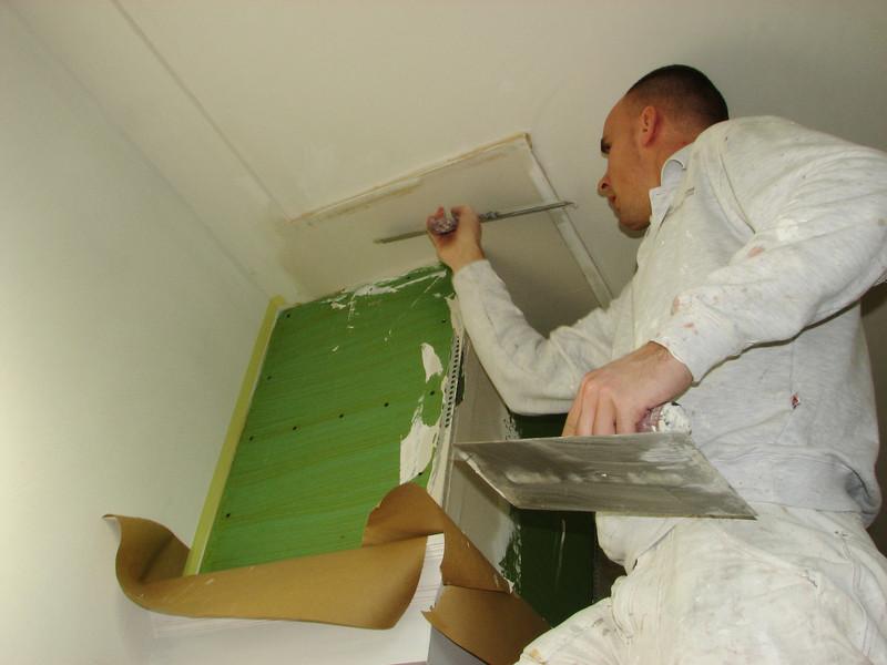 Michael v.d. Kerkhof is plastering the edges of the mantelshelf
