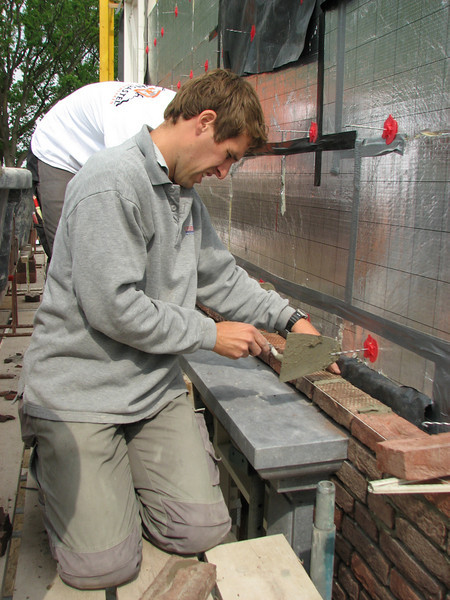 Paul bricklaying the first layer on the iron angle
