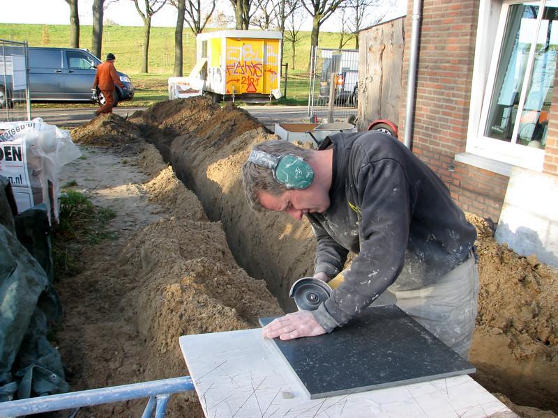 Toine Adriaans grinding tiles of the badroom (Avedo tegelwerken)