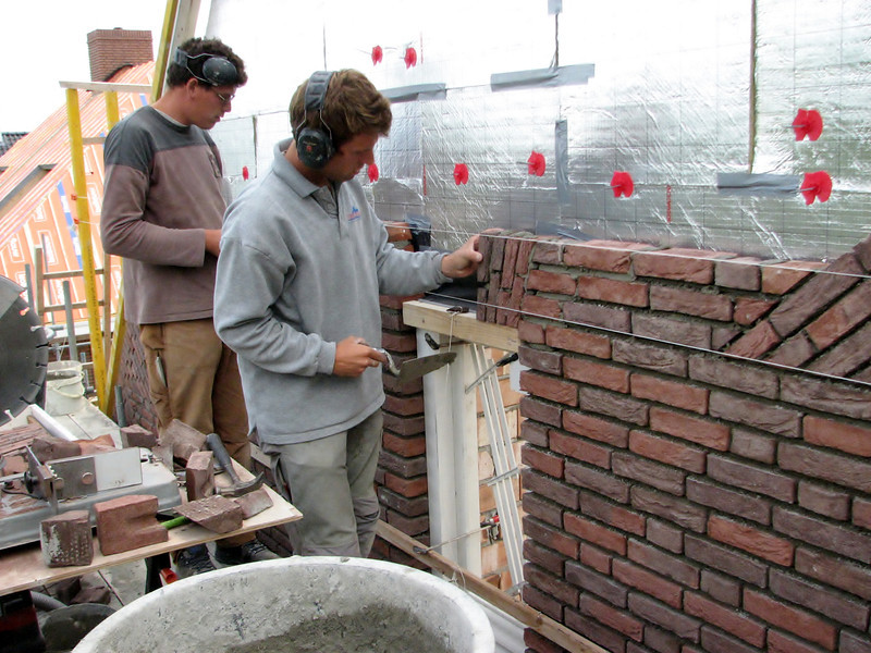 Paul and Twan bricklaying the upright courses of the gable