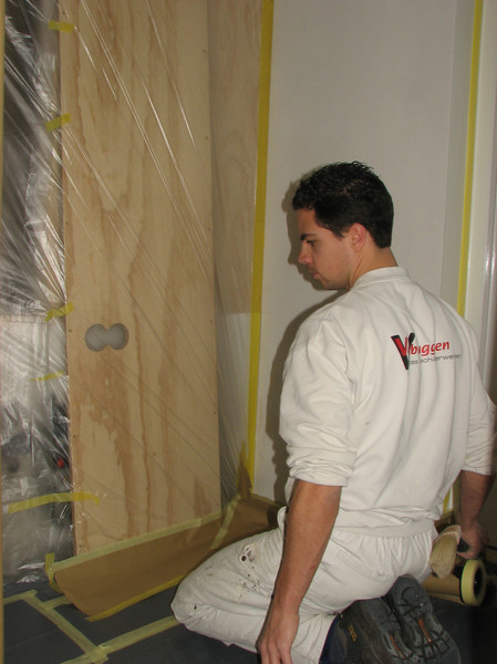John is taping up before spraying the walls and ceiling (firm: Robert v.d. Wetering schilderwerken)