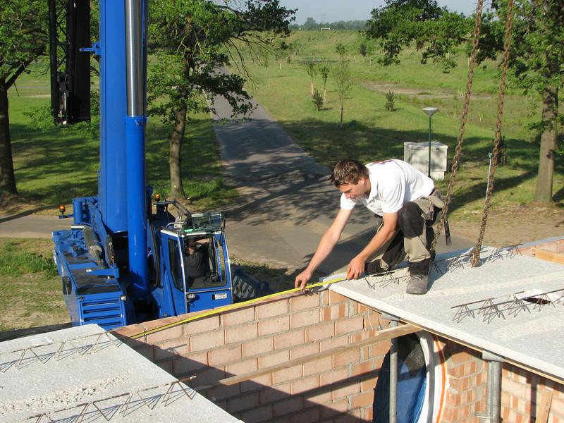 Jarno van Hal measuring and adjusting the concrete floor elements