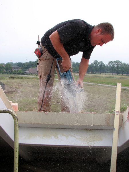 Hans sawing a hole in the roof for the dormer (NL: dakkapel)
